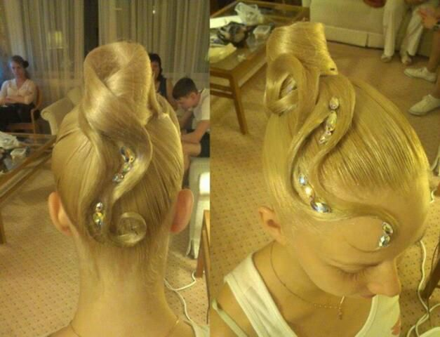 High bun with swirls extending both forwards and backwards with stoning. Great hairstyle for standard. Visit http://ballroomguide.com/comp/hair_make_up.html for more hair and makeup info