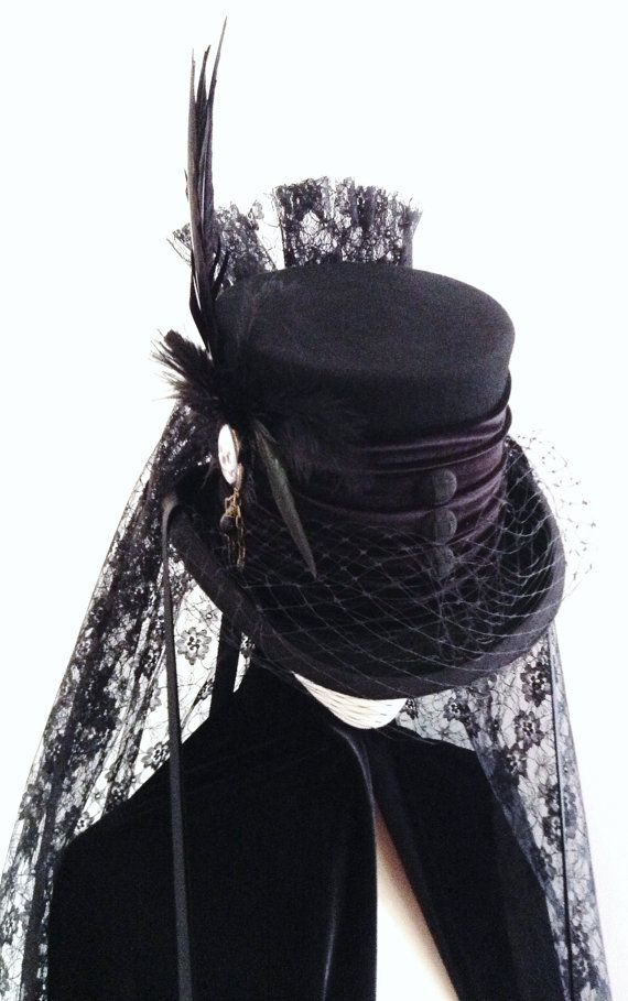 All black top hat with velvet band, silk straps, lace bustle and back veil, front buttons and side ornament with Venetian lace deaths head skull, black feathers and a clutch of 3 raven feathers, finished with a bird cage face veil. Made in Scotland in my own workshop https://www.etsy.com/uk/shop/Blackpin?ref=hdr_shop_menu