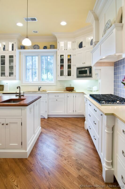 A Lovely Cottage Kitchen With White Cabinets, Wood Floors, And A Beautiful  Wood Hood