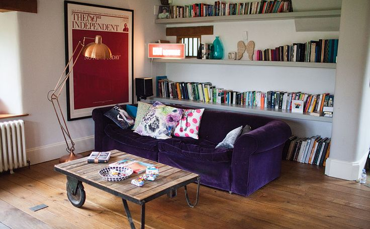 A tall coffee lamp stands next to Jo Whiley's deep purple velvet sofa which is covered with multi-colour cushions.