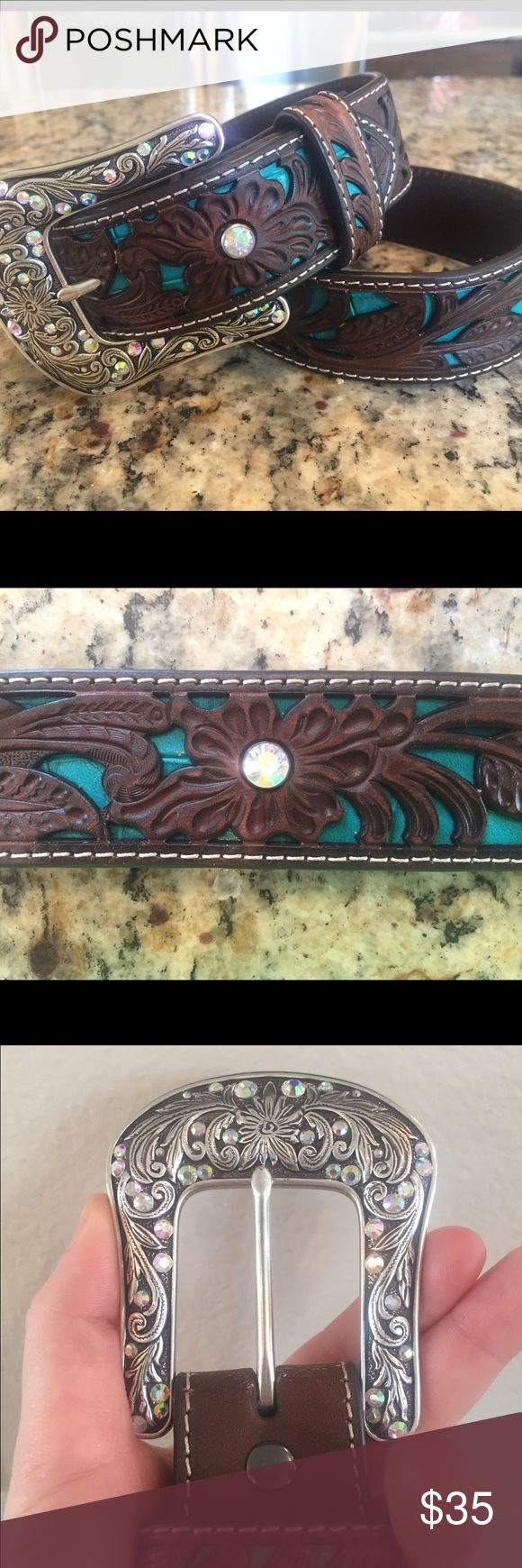 Ariat Leather Rhinestone Cowgirl Bling Belt This Ariat belt is in perfect condition. It's brown leather with a turquoise green - blue underlay. It has white stitching and a flower - floral pattern. It's too small for me and I have not even worn it once (was hoping to lose weight but didn't get there and now it's past the 30 days I can return it). There are no creases in the leather. Not a single jewel is missing. The silver belt buckle is also in perfect condition as shown. Size small. Ariat…