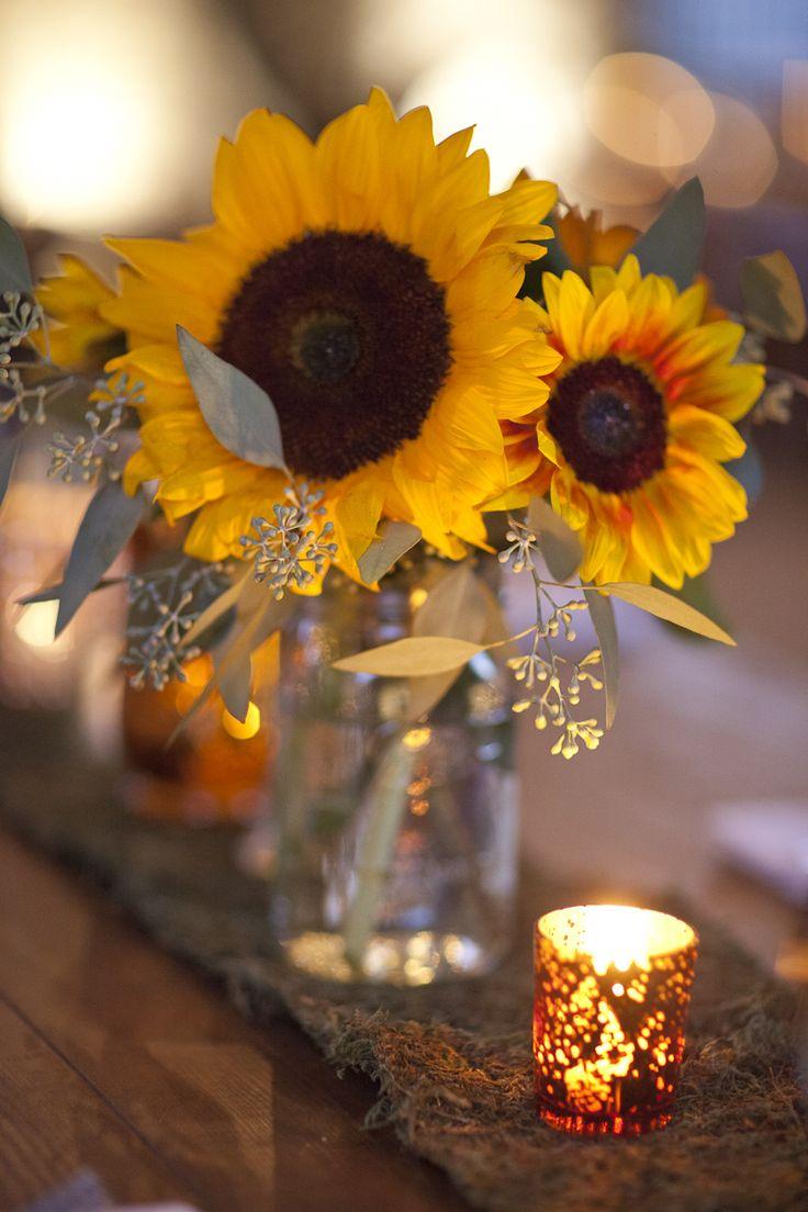 Sunflower centerpieces along a rustic tablerunner.                                                                                                                                                                                 More