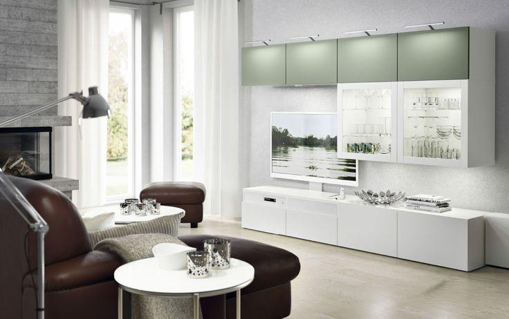 Salón con mueble de TV blanco con cajones blancos y armarios de pared con puertas en verde claro y blanco y paneles de vidrio templado; acabado con un sofá de piel de dos plazas con chaise longue y un reposapiés en marrón oscuro.