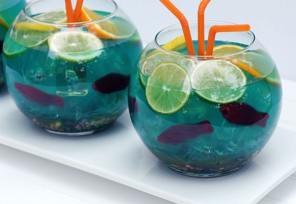 OH YEAAH! FISHBOWL! summer. ☼ -5 ounces of vodka -5 ounces of Malibu rum -3 ounces of blue Curacao -6 ounces of sweet-and-sour mix -A handful of gummy Swedish fish -1/2 cup of Nerds candy -3 slices of lime -3 slices of lemon -3 slices of orange -16 ounces of Sprite -16 ounces of pineapple juice.