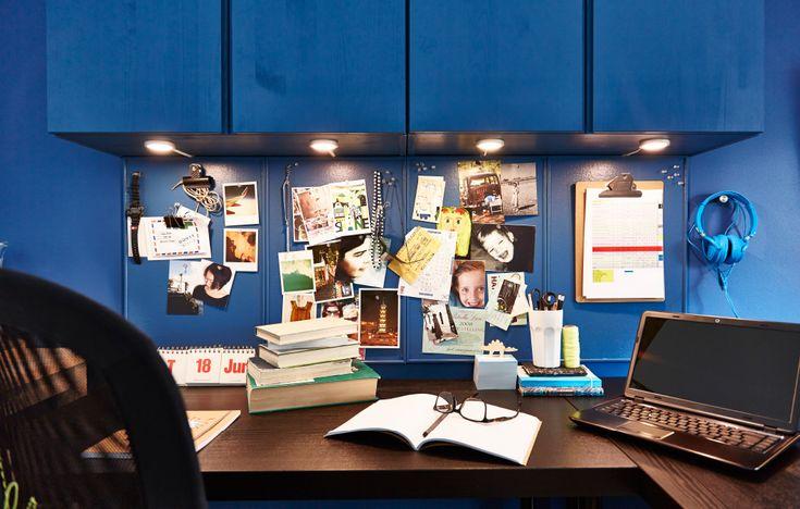 Ein Blick auf eine Reihe von IVAR Schränken in Kiefer an einer Wand. Darunter hängen Pinnwände, die wie die Schränke blau gestrichen wurden. Unter diesen steht ein schwarzer Schreibtisch. Auf dem Schreibtisch steht ein Laptop, an den Pinnwänden hängen verschiedene Fotos und Andenken.
