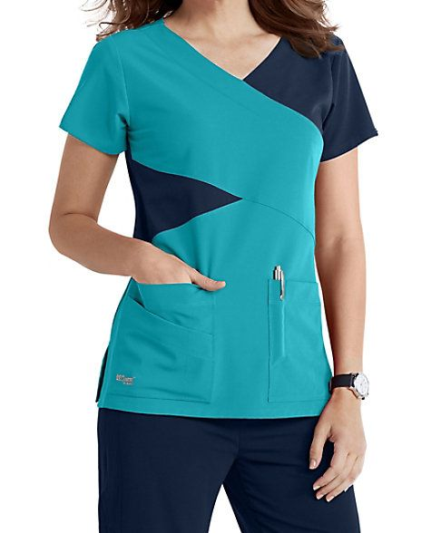 GREY'S IN COLORS Infuse fashion into the workplace with the stylish Grey's Anatomy Signature four-pocket mock wrap scrub top in your favorite color combinations. This cute top creates a unique look by combining detailed style lines and contrast color blocking. Two deep lower pockets, two pen slots and an extra PDA pocket are included to give you plenty of storage options. The super stretch fabric moves with you and is a pleasure to wear throughout your workday. Grey's Anatomy S...