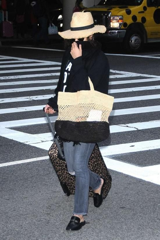 Vanessa Hudgens wearing Loungefly Hello Kitty Rollercase Leopard Print Travel Luggage, Newbark Melanie Mules, Catarzi Straw Hat with Raw Edge Brim and Contrast Black Band and Vix Ibiza Beach Bag