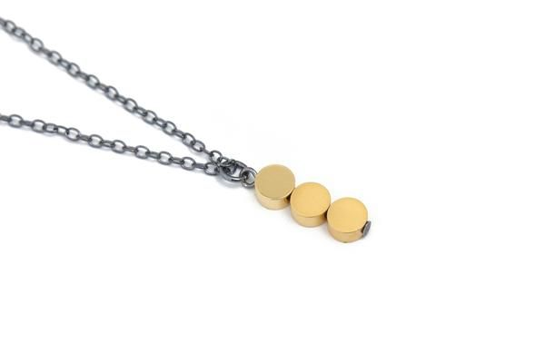 Minimalist necklace in oxidized silver, with three dainty circle beads plated with 16k matte and shiny gold. The necklace has a subtle and unique design with combination of matte and shiny gold, and dark silver.