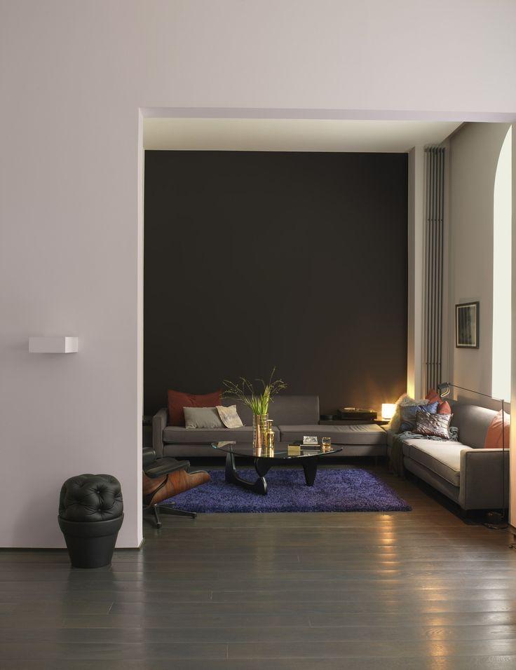 De donkere wand in 'eindeloos' zet een punt. Hier eindigt de drukte van de dag en begint de rust. De lichte muur links in 'intiem' zet dit contrast kracht bij. Toch voelt de ruimte allesbehalve hard aan, dankzij de streelzachte kussens, het tapijt en het warme 'minimalistisch' op de wand rechts. Kleurgebruik: Eindeloos, Intiem en Minimalistisch (collectie: Eenvoud Siert)