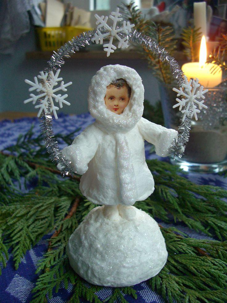 little wintergirl on a big snowball holding a snowflakegarland kleines Wintermädchen auf großem Schneeball mit Schneeflockengirlande