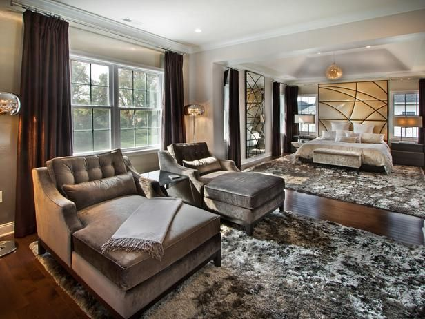 Two chaise longues covered in a sumptuous silver velvet offer a fabulous spot to read or relax in this New Jersey bedroom. Lines carved into a floor-to-ceiling mirror echo the lines of a custom headboard upholstered in gold. Silver shag carpets define separate areas for lounging and sleeping.