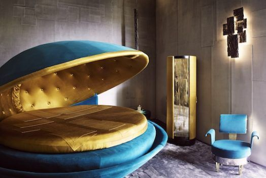 """Tuscany-based architect Roberto Baciocchi's """"precious bedroom"""" — a strange, dreamlike space that recalls Salvador Dalí — is intended to serve as an """"ode to femininity,"""" according to the press material. A huge, kitschy, shell-shaped bed, resembling a turquoise clamshell with a silky golden mouth, seems to float in the middle of the room, whose walls are decorated with cubist collages of silk velvet."""