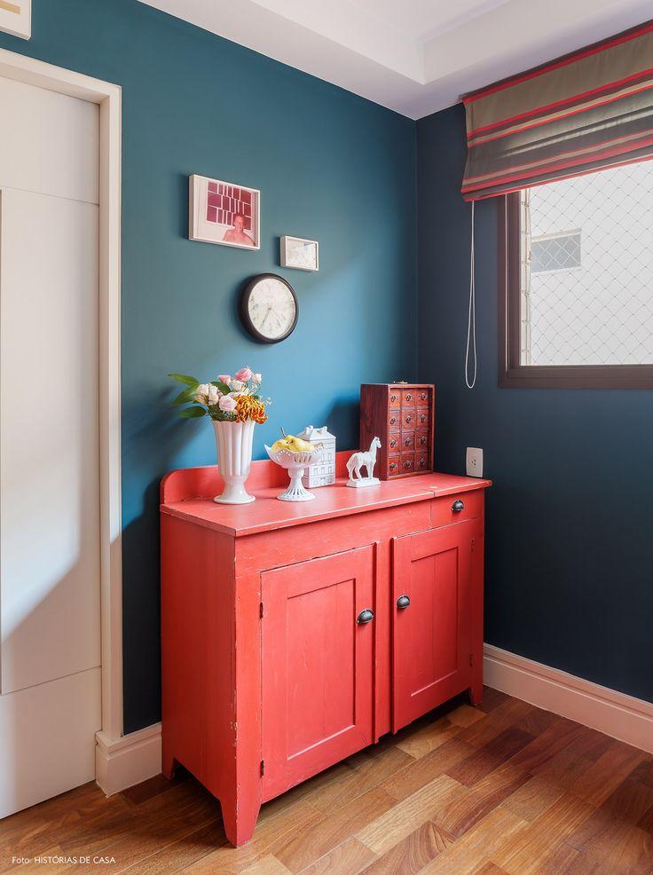 Paredes azuis, armário rústico vermelho e cortina estampada.