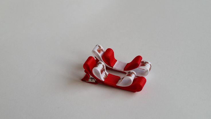 Dwie świąteczne, czerwono – białe spineczki w kształcie kokardek z reniferami. Wymiary kokardki to ok. 1,0 x 5,5cm, klips: pyk 4,5cm.