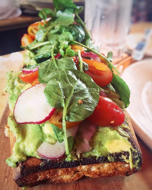 """Cheesecake Factory- Avocado Toast  Described under the """"Super Foods"""" section of their menu as- """"Grilled Artisan Bread Topped with Fresh Avocado, Marinated Tomato, Watercress, Radish and Red Onion. Drizzled with Extra Virgin Olive Oil and Lemon."""""""
