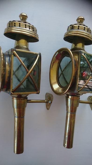 Twee identieke koperen antieke koetslampen met originele branders. 1e helft 20 e eeuw  Twee identieke antieke koperen koetslampen met originele muur afstand houders.De koetslampen hebben originele branders met lont met een mooi patina.De ruiten zijn helemaal heel en hebben een hele mooie geëtste gravure van bloemkoren.Als er brandstof in de lonthouders gedaan wordt kunnen de koetslampen heel gezellig branden.De koetslampen zijn echt een aanwinst in uw interieur en zijn in uitstekende…