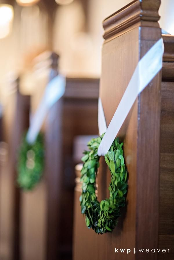 pew markers of petite boxwood wreaths were hung with cream stain ribbon.