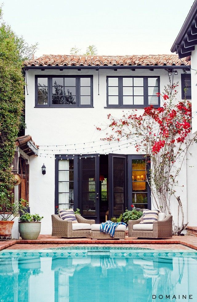 Classic Spanish-style home with terracotta tiled roof and black trim on the windows and French doors that open onto the pool.
