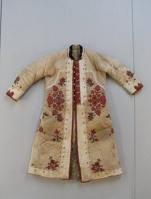 Sheepskin coat, decorated with hand sewn cut leather appliqué stained deep red and pale cream, and coloured embroidery in red, green, purple, blue and pink wools. Two slits enable pockets in inner clothing to be reached, and behind them at the back are two padded leather flaps. The coat fastens with leather buttons and loops.
