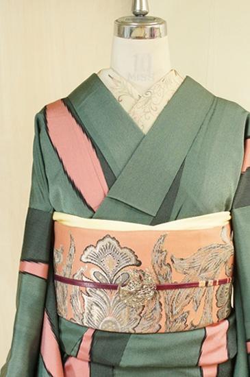 ほのかに緑味をおびたアイビーグレーと黒のバイカラーのストライプが織りなすツートンのグレーに、スモークがかった優しいピンクのよろけ縞が織り出されたモダンでスタイリッシュな正絹御召袷着物です。
