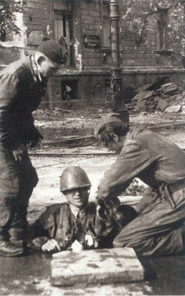 An insurgent from Mokotów is helped out of the manhole at Ujazdowskie alley.