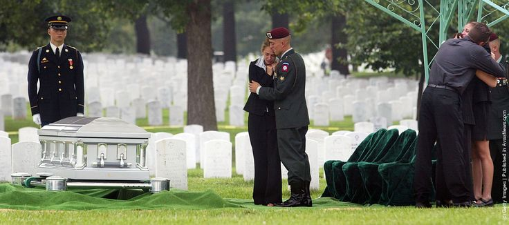 Family and friends console each other during the burial service for U.S. Army Sergeant Chad Keith August 1, 2003 at Arlington National Cemetery in Arlington, Virginia. Keith, 21, of Batesville, Indiana was killed July 7, 2003 when a roadside bomb exploded as his unit was patrolling Baghdad, Iraq. Keith was a gunner with Company D, 2nd Battalion of the 325th Infantry, based at Fort Bragg, North Carolina. (Photo by Joe Raedle/Getty Images)