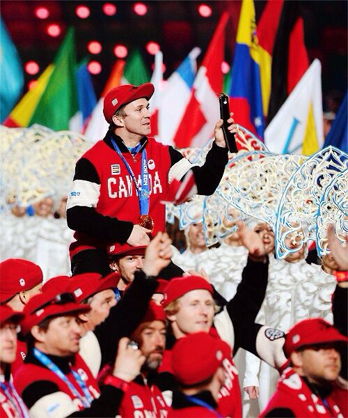 Martin St. Louis rides on Mike Smith's shoulder during the Winter Olympics Closing Ceremony.