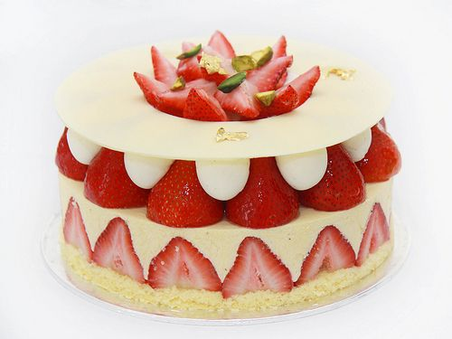 Topped with white chocolate and layered generously with strawberries, vanilla mousse and vanilla chantilly cream on a sponge base