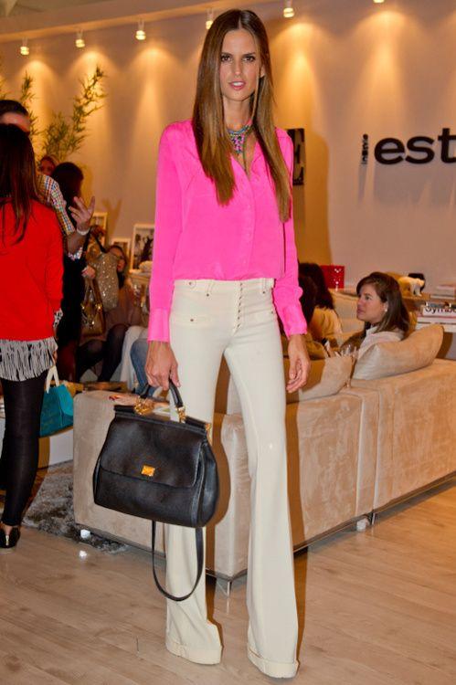 Hot pink top, white pants, black bag, and mega long legs