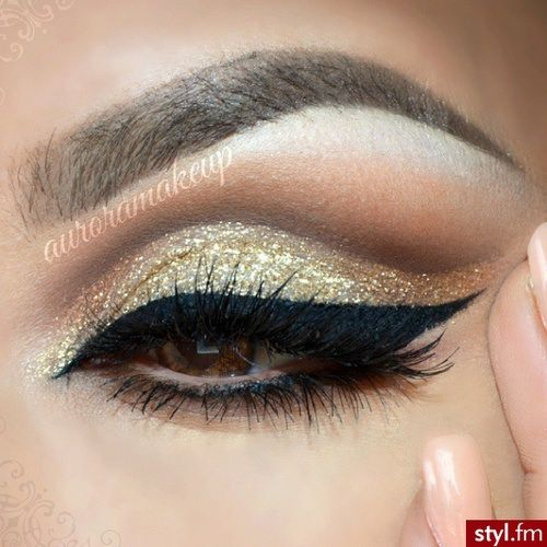 Beautiful cut crease eyeshadow makeup with gold and brown colors and dramatic black eyeliner.