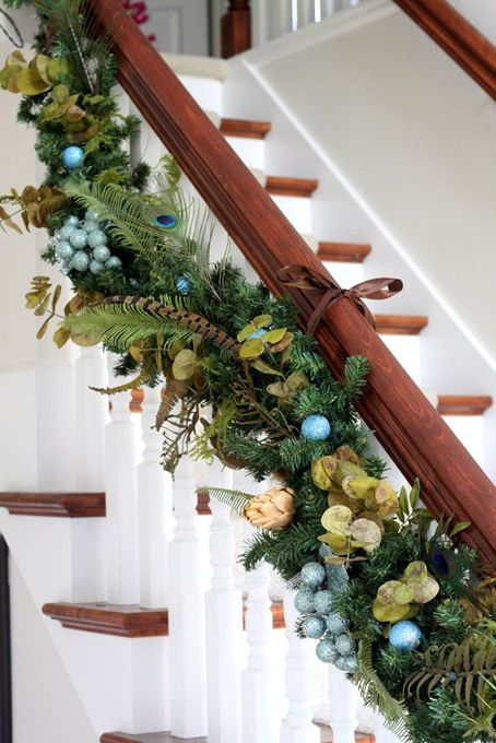 Christmas garland tied to stairs with ribbon
