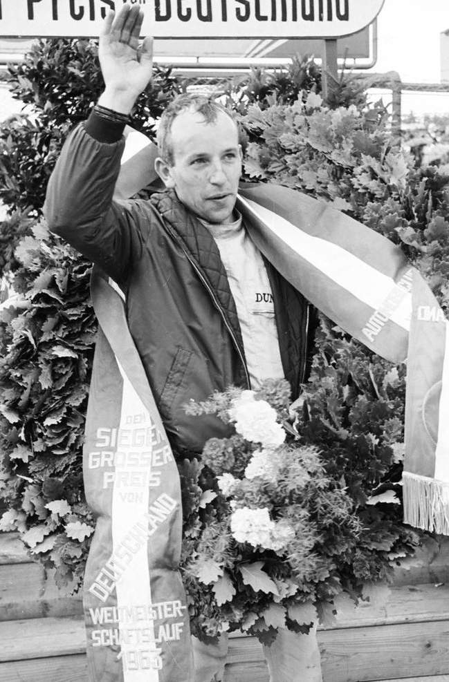 John Surtees (Eng). F1 World Champion (1964). GP starts 111. Poles 8. Wins 6. Podiums 24. 500cc Motorcycle World Champion 4 (1956,58,59,60). 350cc Motorcycle World Champion 3 (1958,59,60). Only person to win world championships on two and four wheels.