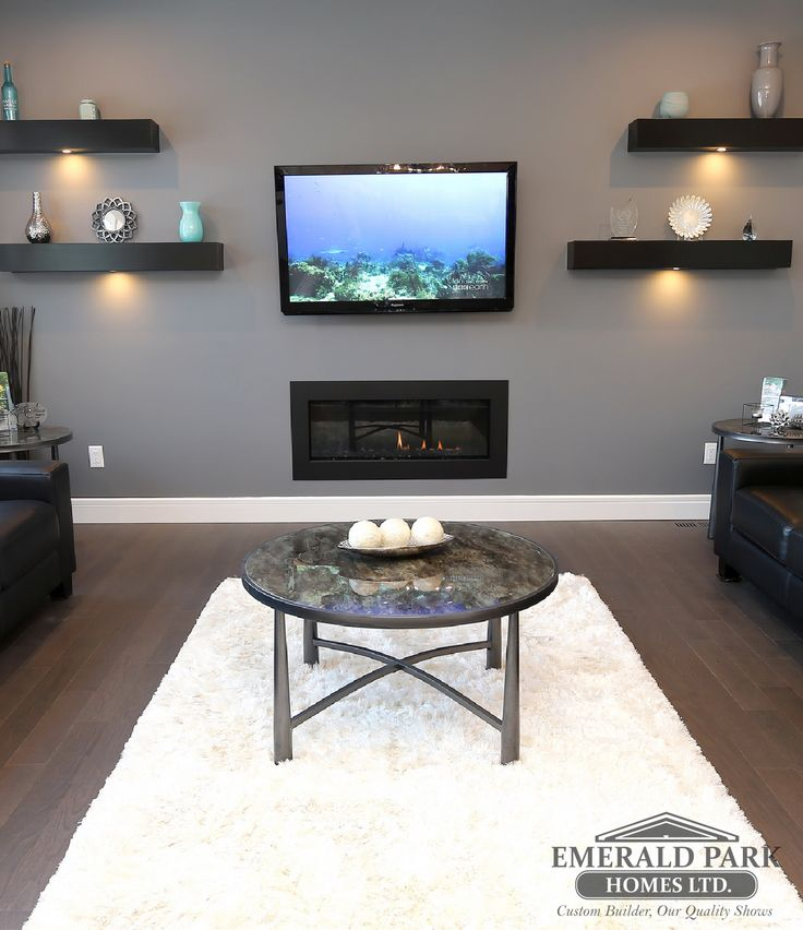 Open concept living room with floating shelves surrounding the linear fireplace