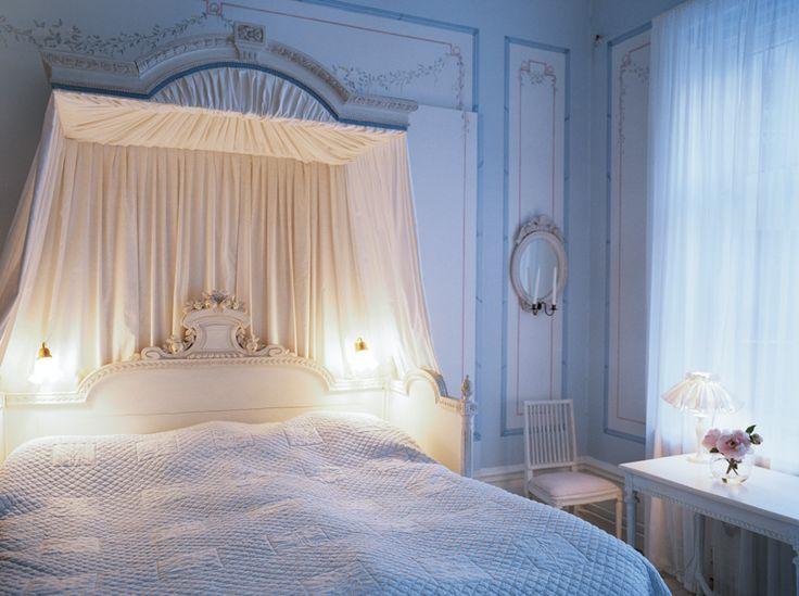 Romantiskt sovrum i svalt blekblått. Den pampiga sängen är en äkta älskarinnesäng från Tullgarns slott. Här tog Sophie Hagman emot hertig Adolf Fredrik, bror till Gustav III. Ursprungligen var sängen helt förgylld.
