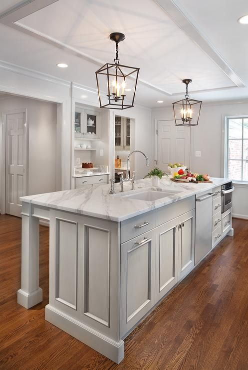 White and gray kitchen features a white ceiling framed with glossy gray beveled trim accented with a pair of Darlana Medium Lanterns illuminating a light gray center island topped with calacatta marble fitted with a sink and deck mount faucet placed next to a stainless steel dishwasher and pull out microwave drawer.