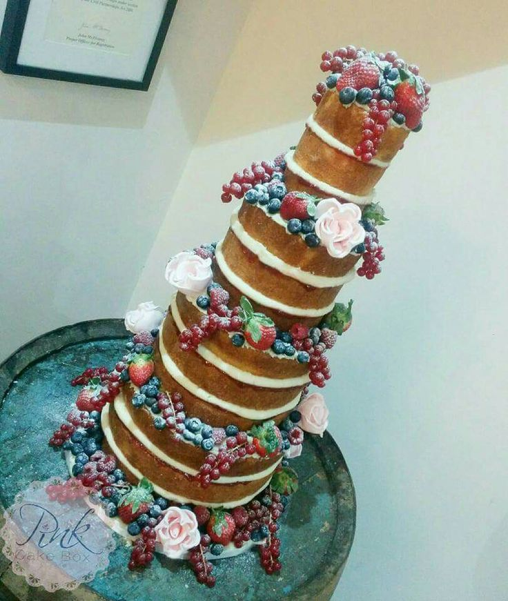 4 tier naked wedding cake with fresh berries and sugar flowers