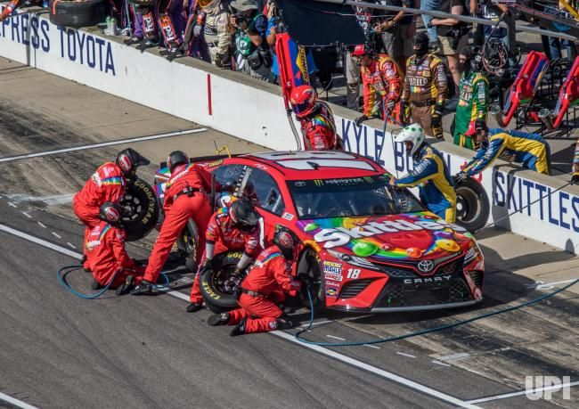 Kyle Busch's crew goes to work during a pit stop after winning Stage 1 of the 2017 Brickyard 400, at the Indianapolis Motor Speedway on…