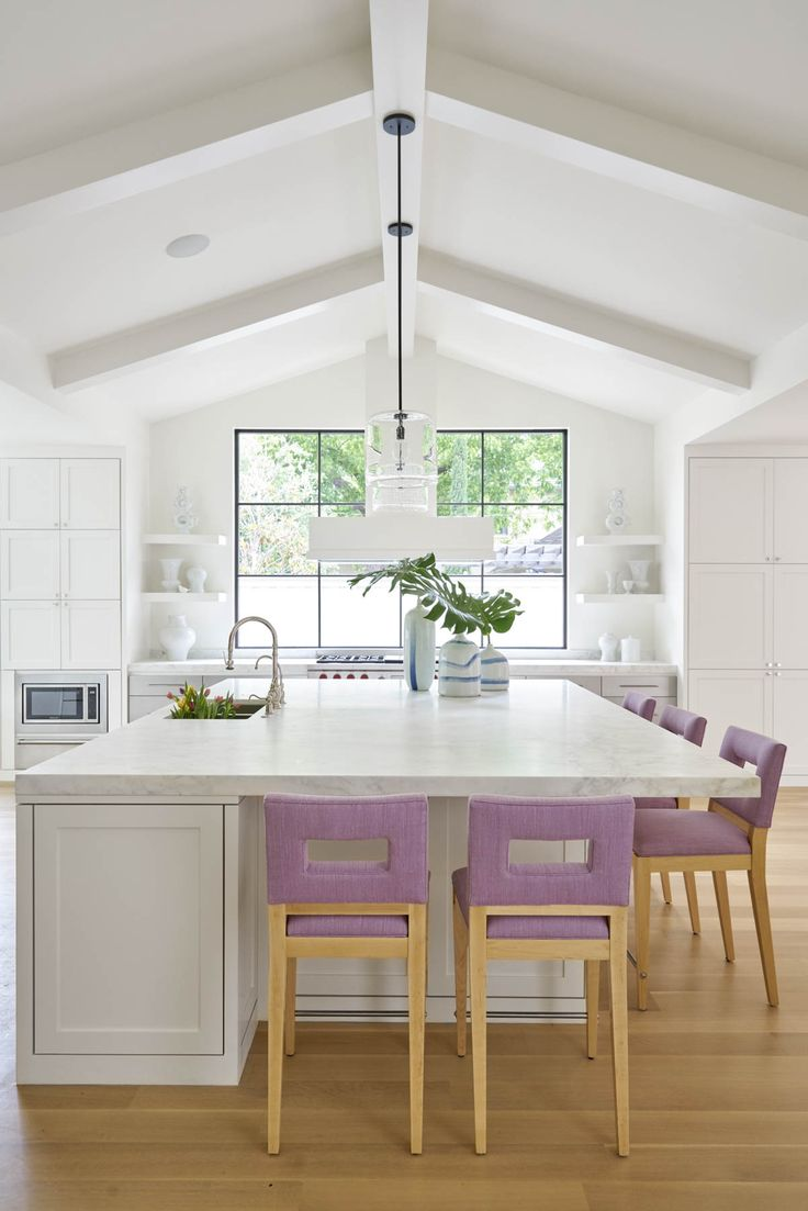 white kitchen with large island and lavender barstools | gray and blue jars with leaves from blue print | design by collins interiors | blueprintstore.com
