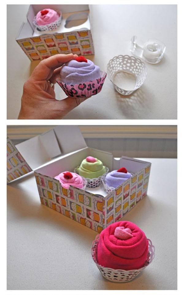 Söta muffins av små sparkdräkter och strumpor i en fin förpackning blir en rolig och uppskattad present till den blivande mamman. Klicka för enkla bildinstruktioner.