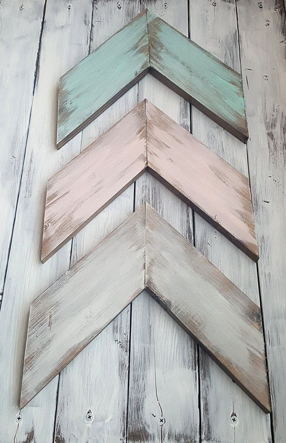 *All of my handmade items are made to order*  These unique, handmade painted and distressed wooden arrows will add character and style to your gallery wall.  These Arrows come is a set of three Each arrow containing two pieces of wood bound at the back with a bracket  This set of distressed colors include: Ivory Blush Mint  If you would like different color options, that is not a problem. Just message me first so I can be sure to accommodate These also come with a 3 saw-tooth hangers for…