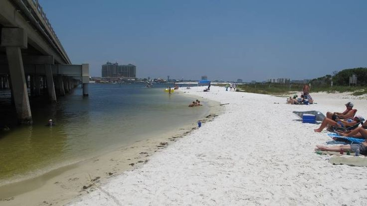 Beachgoers enjoy the shallow beach under a highway bridge in Destin, Fla. The beach is under the control of Eglin Air Force Base, but the public is welcome to use a portion of the beach.