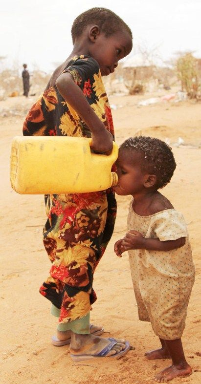 This photo shows a young child drinking from an old jug. Most of the people in Haiti don't have any clean water. They drink out of the same streams that they wash their cars in, that they wash their clothes in, that they take baths in. It's very dirty and unclean but it is all they have.