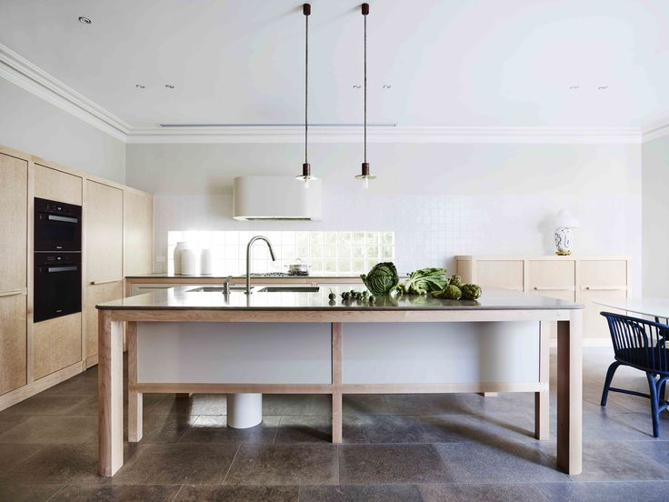 Sydney heritage house kitchen. French limestone floors and bench tops, burled maple veneer, Dominico Mori wall tiles from Boffi and Viabizzuno pendant light fittings.