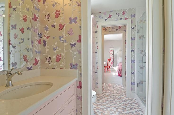Gray and pink girl's bathroom features walls clad in purple and gray floral wallpaper lined with a pink washstand topped with white quartz under a curved frameless mirror alongside a pink and gray penny tiled floor,.