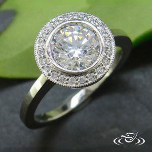 Antique style halo full bezel mounting for 7.25mm center stone with (22)bead set Diamonds around the center (0.14ctw) with milgrain detailing around the halo, polished finish