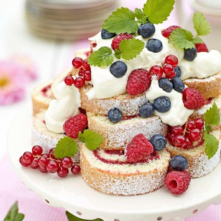 Sommartårta med rulltårteskivor, färska bär och grädde.