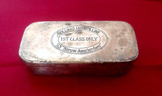 A nice weighty little tin box , with hinged lid, which was given to 1st Class passengers aboard the SS Nieuw -Amsterdam in the 1930s and 40s.  The lid is stamped.. HOLLAND AMERICA LINE  1ST CLASS ONLY SS  Nieuw-Amsterdam  Tin measures 3.5 by 1.6 and is 6/8 tall.  A lovely piece of Maritime memorabilia.