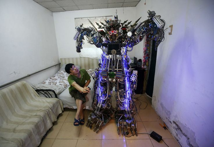 Chinese inventor Tao Xiangli controls his self-made humanoid robot with a remote controller as he poses with it during a photo opportunity at his house located in a old residential area in Beijing August 8, 2013.