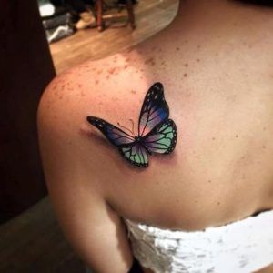 #1. Gaudy 3-D Butterfly Tattoo on Shoulder-Blade The tender butterfly tattooed on the left shoulder-blade in a tridimensional manner reveals the boundless freedom and independent. The image was completed with gaudy colors: lilac, green, blue, black and purple. The fluttering light-winged creature shows the desire for change and transfiguring. #2. Graceful Butterfly with Inscription on …