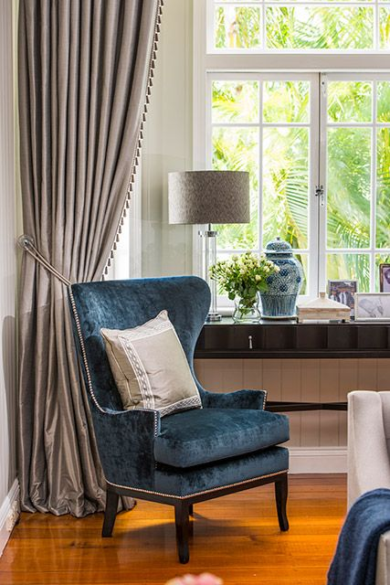 INTERIORS BY HIGHGATE HOUSE Ink Blue velvet chair with chrome stud detaling. curtains with decorative trimmings